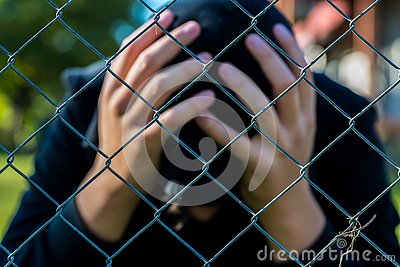 Young unidentifiable teenage boy holding hes head at the correctional institute ,conceptual image of juvenile delinquency