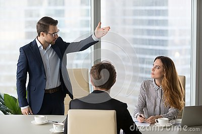 stock image of mad male worker asking female partner leave meeting