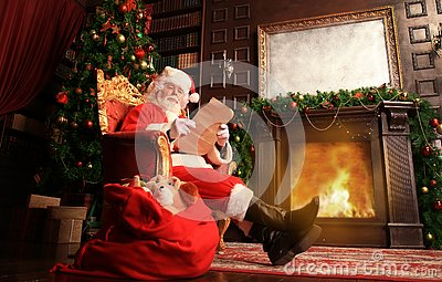 Portrait of happy Santa Claus sitting at his room at home near Christmas tree and reading Christmas letter or wish list.