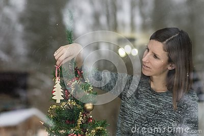 Young brunette hanging wooden ornament on Christmas tree