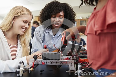 stock image of teacher with female pupils building robotic vehicle in science lesson