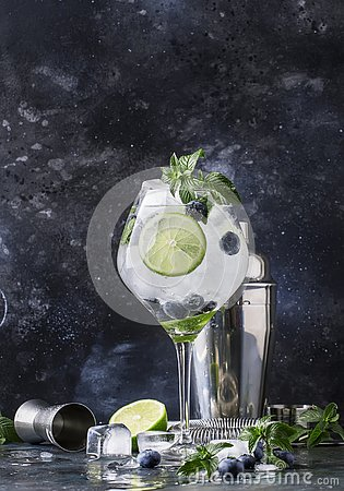 Summer alcoholic cocktail blueberry mojito with rum, green mint, lime and crushed ice, bar tools, gray bar counter, selective