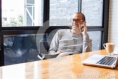 Cheerful asian male small business owner talking on phone with customer while sitting in office. Copy space.
