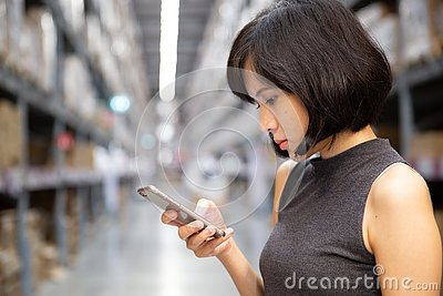 stock image of a beautiful woman using smart phone at the warehouse