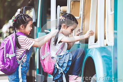 Asian pupil kids with backpack holding hand and going to school
