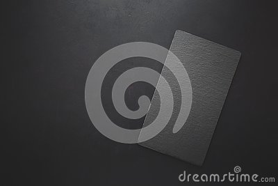 Top view on rectangle black slate plate on rustic dark background. Copy space. Toned