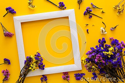 Colorful bouquet of dried autumn flowers lying on a white frame on yellow paper background. Copy space. Flat lay. Top view