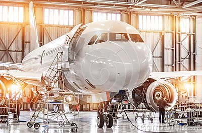 Passenger commercial airplane on maintenance of engine turbo jet and fuselage repair in airport hangar. Aircraft with open hood on
