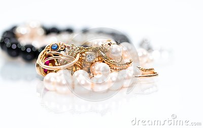 Real gold jewlery, diamonds, gems, rings, neckless with pearls close up shot