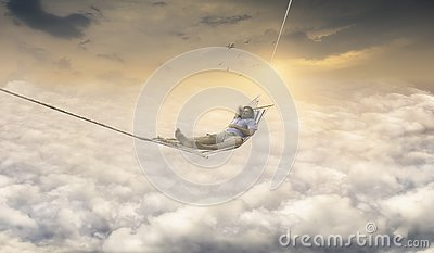 Man Dreaming in Rocking Net Above Sky