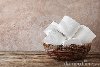 Bowl with toilet paper rolls on wooden table