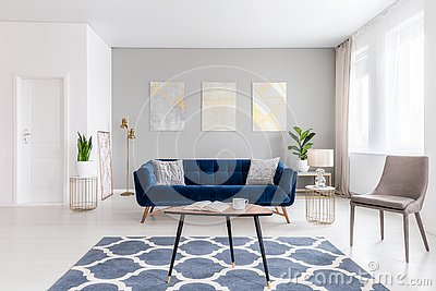 Open space living room interior with modern furniture of a navy blue settee, a beige armchair, a coffee table and other objects in