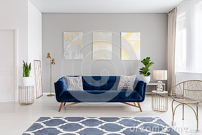 An elegant navy blue sofa in the middle of a bright living room interior with gold metal side tables and three paintings on a gray