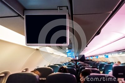 stock image of interior of passenger airplane and blank entertainment screens