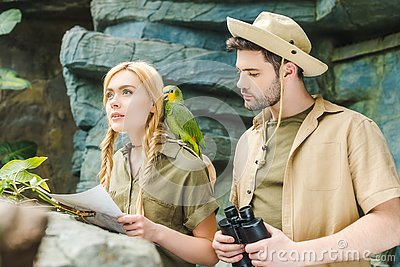 beautiful young couple in safari suits with parrot trying to navigate