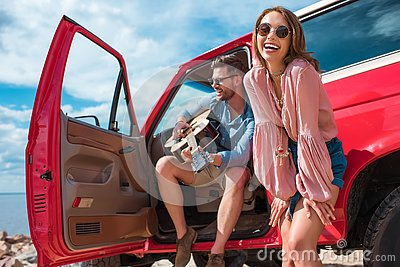 young man playing guitar near car with cheerful girlfriend