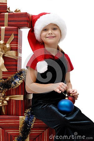 Cute little girl in a Santa Claus cap with Christmas gifts, isol