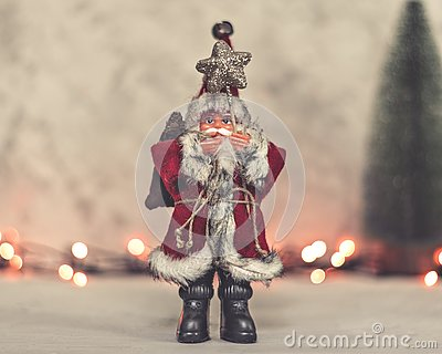 Santa Claus toy brings Christmas tree at blue snowy night bokeh background and blurred lights foreground.