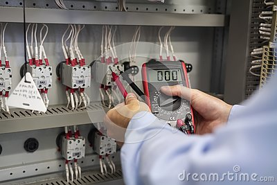 Multimeter in hands of electrician closeup. Service works in electrical box. Maintenance of electric panel