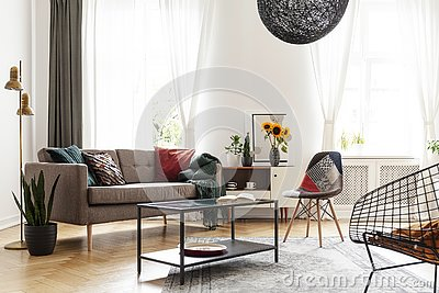 Simple brown sofa with cushions in an eclectic, white living room interior with natural light coming through big windows.