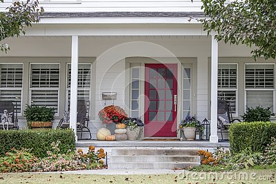 Entrance and porch to pretty house with Autumn and Halloween decorations and fall leaves blowing in the wind - curb appeal