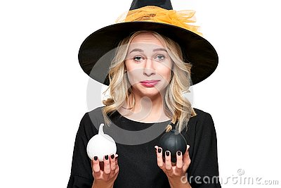 Gorgeous Halloween Witch trying to suppress laughter while holding tiny pumpkins. Cheeky woman in witches hat.