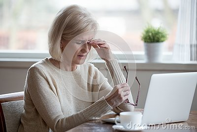 Fatigued mature woman taking off glasses suffering from eye stra
