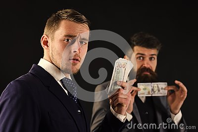Meeting of reputable businessmen, black background. Man on serious face hold roll made out of dollar, money, pay to