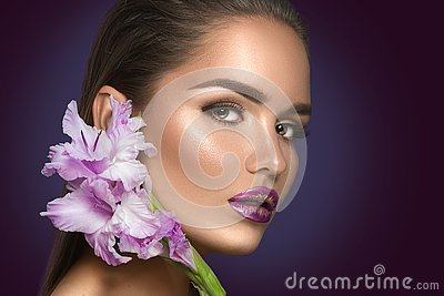 Beauty fashion brunette girl with gladiolus flowers. Glamour woman with perfect violet trendy makeup