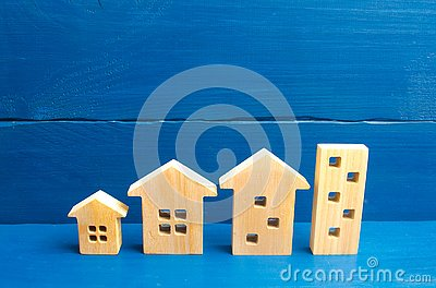 stock image of houses stand in a row from simple to large. concept of urbanization and population density. the growth of cities, the construction