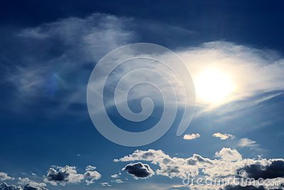 Bright sun with aureole making its way through the cirrus clouds