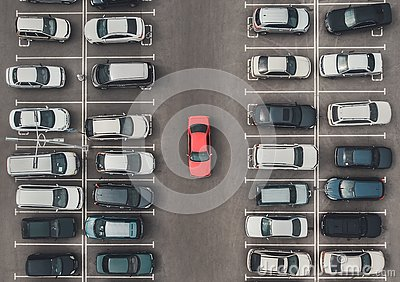 Top view of the crowded Parking lot with quadcopter or drone. Original bright automobile among the grey of mediocre cars. Parking