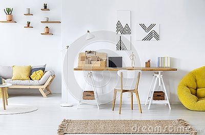 Modern home office interior with graphics, desk, sofa and yellow pouf