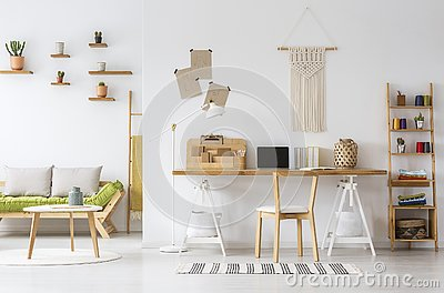 Natural home office interior desk organizer, macrame on a wall, shelves and couch