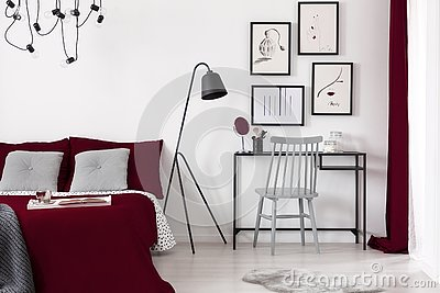 Gallery of illustrations on a white wall above a small desk which is next to a black metal lamp and a burgundy bed in a modern b