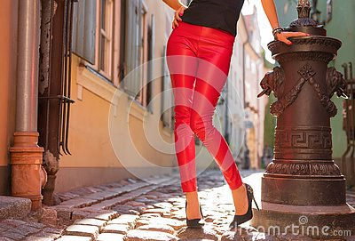 Woman wearing bright red leather trousers and high heels