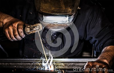Professional mask protected welder man working on metal welding and sparks metal