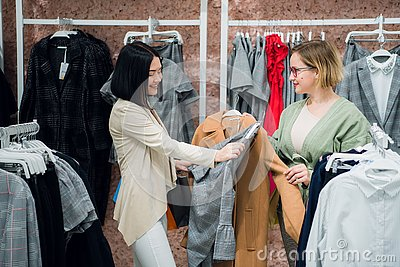 Sales consultant helping chooses clothes for the customer in the store. Shopping with stylist concept. Female shop