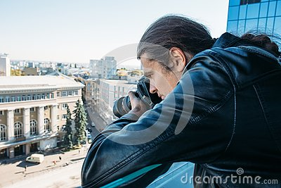 Investigator or private detective or reporter or paparazzi taking photo from balcony of building with professional camera