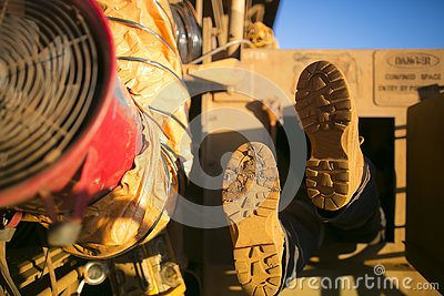 Rope access miner wearing safety boot harness, helmet entering into confined space