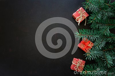 Christmas Border. Fir tree branches with gift boxes on dark wooden background.
