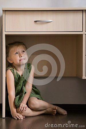 Childhood fears. Scared little girl hiding under the table