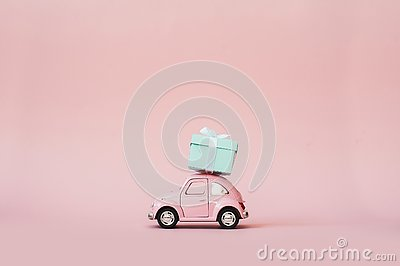 Pink toy retro model car delivering gift box for Valentine`s day on pink background. Volkswagen Beetle on pink background.