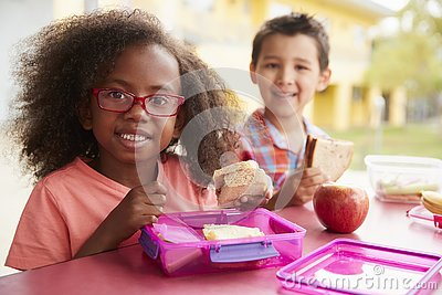 Two young school kids eating their packed lunches together