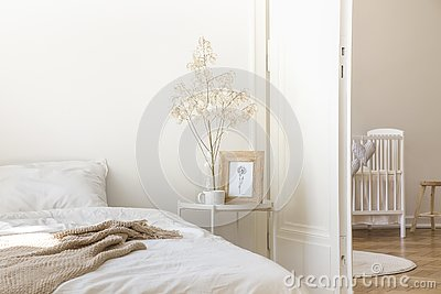 White metal bedside table with coffee mug, twig in glass vase and simple poster in frame placed by the bed