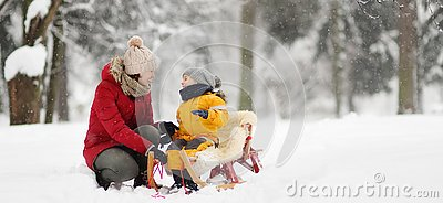 Mother/nanny talk with small child during sledding in winter park