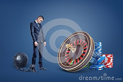 A sad businessman chained to an iron ball stands near a casino roulette and chip stacks.