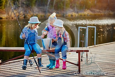 Three little happy girls brag about fish caught on a fishing pole. Fishing from a wooden pontoon