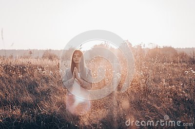 Girl closed her eyes, praying outdoors, Hands folded in prayer concept for faith, spirituality and religion. hope, dreams concept.