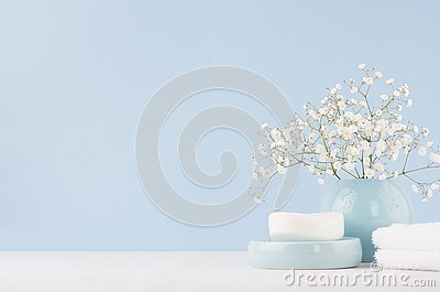 Elegant accessories for dressing table - soft pastel blue ceramic bowls, white flowers, products for skin and body care on white.